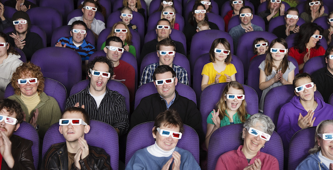 A large audience wearing 3D glasses in a darkened movie theater.
