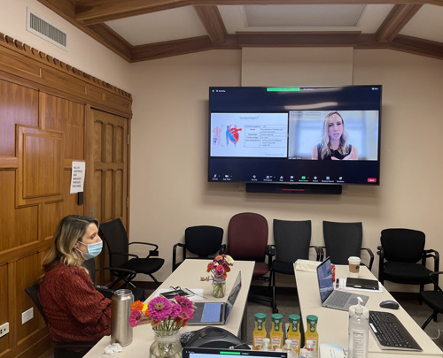 Janna Landsperger, MSN, RN, ACNP, seated, helps conduct the ACNP/PA Critical Care Boot Camp from a conference room in Medical Center North. Presenting on screen is Allison Wynes, a nurse practitioner at University of Iowa Hospitals and Clinics.