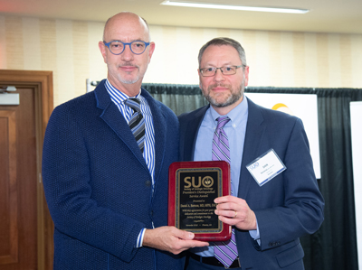 Daniel Barocas, MD, MPH, right, receives the Society of Urologic Oncology's Distinguished Service Award from Christopher, Evans, MD.