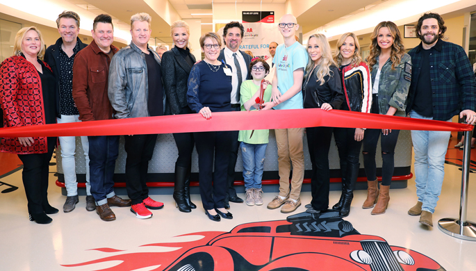 From left, Kathryn Carell Brown, Joe Don Rooney, Jay DeMarcus and Gary LeVox of Rascal Flatts, Allison DeMarcus, Meg Rush, MD, MMHC, Scott Borchetta, Maddie Wright, Dalton Waggoner, Sandi Spika Borchetta, Sheryl Crow, Carly Pearce and Thomas Rhett prepare for the ribbon cutting of the Big Machine Neighborhood on the new 11th floor at Children's Hospital.