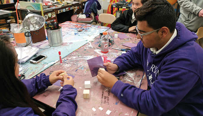 Art students from Father Ryan High School prep the cubes for VUMC patients by sanding and painting their surfaces.