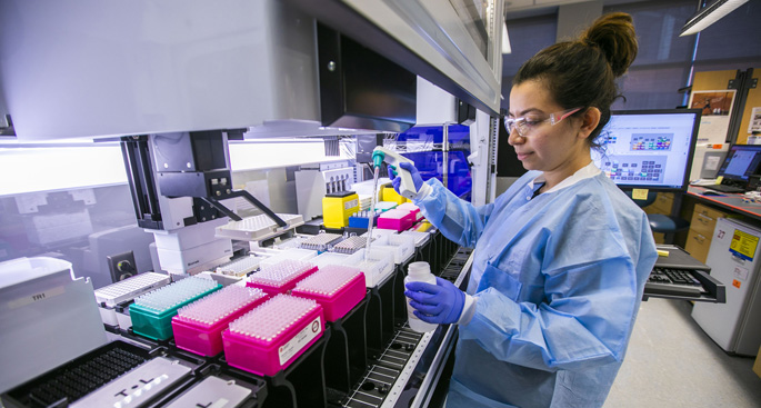 "Research assistant Mahsa Majedi loads reagent used in DNA sample preparation in the genomics lab. She is part of a team of more than a dozen people at VUMC who are ""sprinting"" to develop — within 90 days — an antibody-based treatment to stop the spread of the Zika virus."
