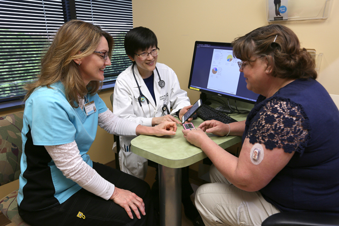 Shichun Bao, MD, PhD, center, and Brenda Weedman, RN, BSN, discuss continuous glucose monitors with patient Sherry Neergaard.