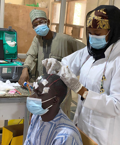 Mohammed Umar, chief EEG tech for the SEED project, supervises Community Health Workers training in EEG. Here, he looks on as Hauwa Yusuf Nuhu places EEG electrodes on Musa Sanusi Muhammad.
