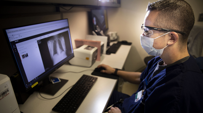 Tyler Barrett, MD, MSCI, reviews an imaging scan in the VUAH Emergency Department, where a dedicated process ensures follow-up of suspicious images unrelated to a patient's injuries. (photo by Susan Urmy)