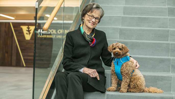 Mary Jo Gilmer, PhD, MBA, with Misha, a teddy bear goldendoodle that provides animal-assisted therapy. (photo by Anne Rayner)