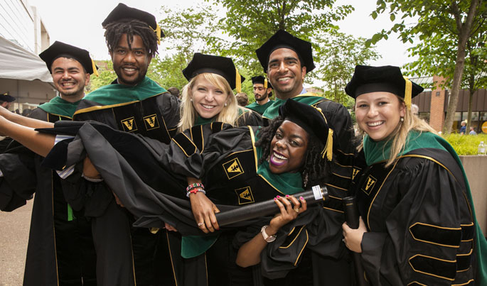 Jacqueline Harris receives a lift from fellow School of Medicine graduates, from left, Nick Baddour, Majaliwa Mzombwe, Jessica Lindsay Burris, Nikhil Chavali and Megan Shroder.