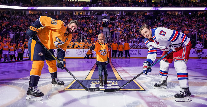 Children's Hospital patient ambassador Katie Shepherd, who served as Mayor of Smashville during Hockey Fights Cancer, drops the puck with the Predators' Roman Josi, left, and New York Ranger Jesper Fast.