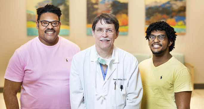 Jeremy Kerr, left, and his son Tyler, right, pose with Sam McKenna, MD, DDS, who performed corrective jaw surgery to repair their underbites and crossbites.