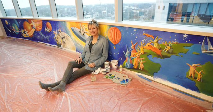 "Artist Rachael McCampbell poses with her mural, ""Space Bunnies,"" on the 11th floor or Monroe Carell Jr. Children's Hospital at Vanderbilt."