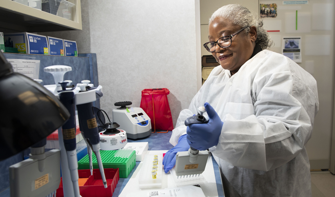 Medical laboratory scientist Gladys Garrison, MT, MS, loads reagents to prepare DNA samples for analysis in the VUMC Molecular Diagnostics Lab.