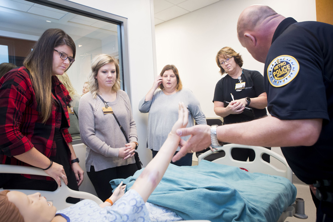 A Metro Nashville Police Department crime scene investigator uses a nursing mannequin with simulated bruising to demonstrate how to photograph assault injuries to VUSN students Erin Talbott, left, Lauren Lariscy, Jennifer Pricher and Rita Peters.