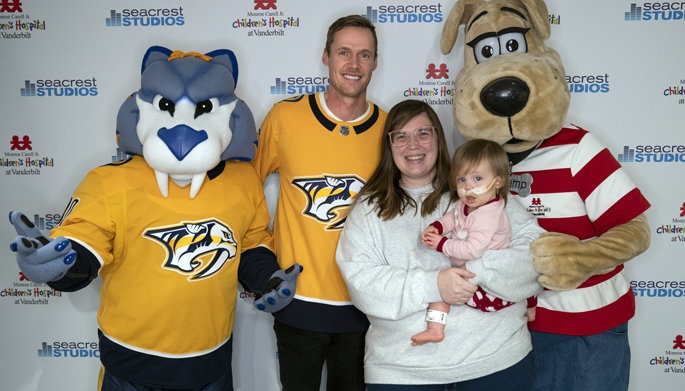 Nashville Predators mascot Gnash and goaltender Pekka Rinne, joined by Children's Hospital mascot Champ, pose for a photo with patient Charlotte Merryman, 17 months, and her mom, Shelby, during a recent visit to Seacrest Studio at Children's Hospital.