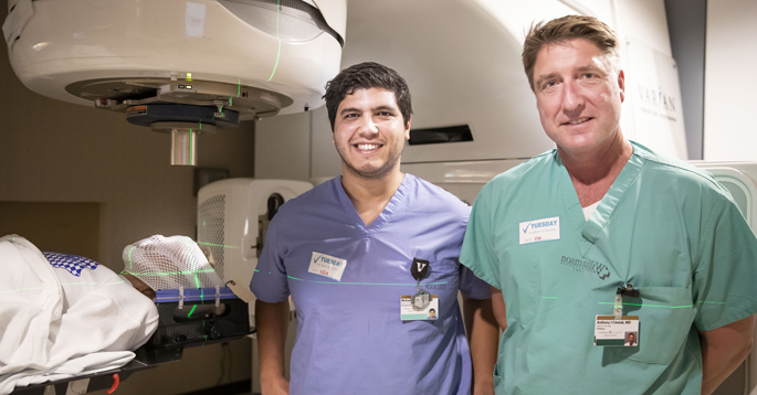 Mohamed Khattab, MD, left, and Anthony Cmelak, MD, are studying the use of a linear accelerator to target the areas in the brain's limbic system that control the pathway for obsessive compulsive disorder. (photo taken prior to social distancing)
