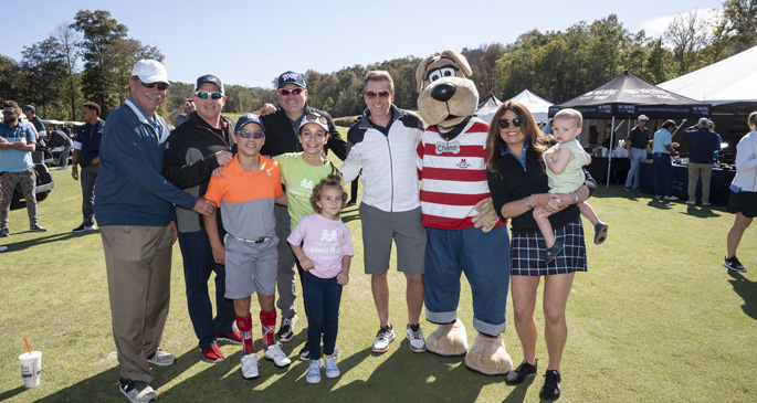 Rascal Flatts members kick off the fourth-annual Rascal Flatts Celebrity Golf Classic with Children's Hospital patient ambassadors, event sponsors and Champ, the hospital's mascot. Shown here are patient ambassadors Logan Miller, Jessica Meyer, Caroline Lantz, and Levi Ray (in front) with, from left, Delta Dental's Phil Wenk, Gary LeVox, Jay DeMarcus, Joe Don Rooney, Champ, WME's Kristin Cantrell.