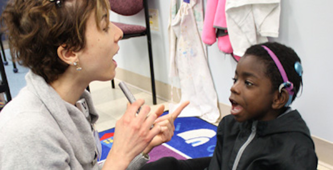little boy with cochlear implant interacting with his teacher