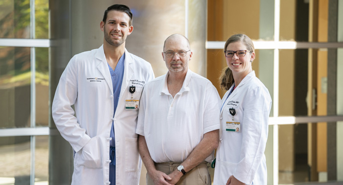 Patient Keith Sanford, center, had a shorter hospital stay and did not take any prescription pain medications after Joseph Broucek, MD, and Meredith Duke, MD, performed a minimally invasive, robot-assisted abdominal hernia repair.