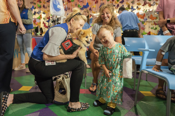 Patient Cole Ringer, 2, and his mother, Emilie, are delighted to interact with volunteers Swoosh the dog and his handler, Michelle Thompson, at the annual Dog Days of Summer Paw-ty on July 17 at Monroe Carell Jr. Children's Hospital at Vanderbilt. The event featured a dog show, a meet-and-greet with pet volunteers and updates on the Mars Petcare Pet Therapy Fund and the upcoming arrival of Children's Hospital's facility dog.