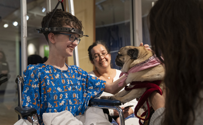 Internet sensation Doug the Pug, who recently starred in a Super Bowl commercial, visited patients and families in Seacrest Studio at Monroe Carell Jr. Children's Hospital at Vanderbilt. Known for his funny costumes and adventures, the Nashville dog's videos and photos have been viewed by millions on social media.  Shown here, patient John Hawkingberry III, 13, accompanied by his mother, Melissa, pets Doug, being held by his owner, Leslie Moser.