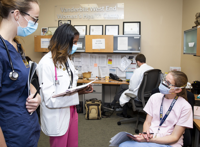 Rondi Kauffmann, MD, MPH, seated, reviews a patient's medical history with Vanderbilt University School of Medicine students Natasha Hughes, far left, and Candace Grisham, during a recent surgical clinic.
