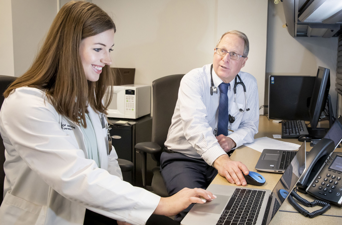 Fourth-year VUSM student Emily Long assists Paul Epstein, MD, as he conducts telehealth visits with patients of the Vanderbilt Eskind Diabetes Clinic.
