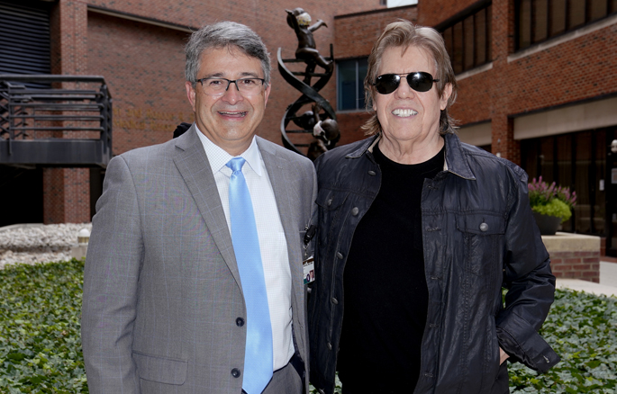 """Rocker George Thorogood, right, shown here with Ronald Alvarez, MD, MBA, recently made a donation to Vanderbilt-Ingram Cancer Center (VICC) from the Marla Thorogood Memorial Fund for Ovarian Cancer Research and plans to do more in memory of his wife, Marla, who he lost to ovarian cancer in 2019. In September, a limited-edition T-shirt featuring the Destroyers logo will be available for purchase online and at shows during the """"Good to Be Bad Tour."""" Sales will benefit cancer research at VICC."""
