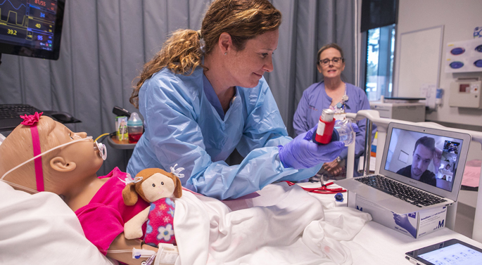 "Pediatric instructor Lesley Ann Owen waits for instructions from student Alec Bradbury before providing respiratory care to their pediatric ""patient."" Instructor Jennifer Hicks observes and coaches, just as she would in a clinical setting."