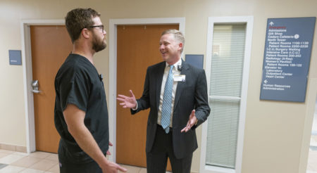 Jay Hinesley, MHA, chief executive officer of VWCH, right, talks with staff members during orientation.