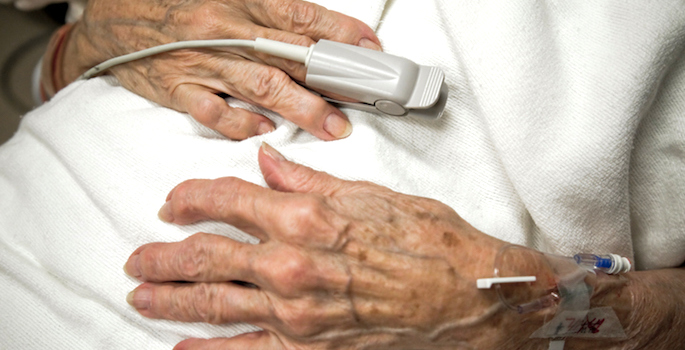 hands of elderly white woman in hospital with oxygen monitor on finger and iv in arm