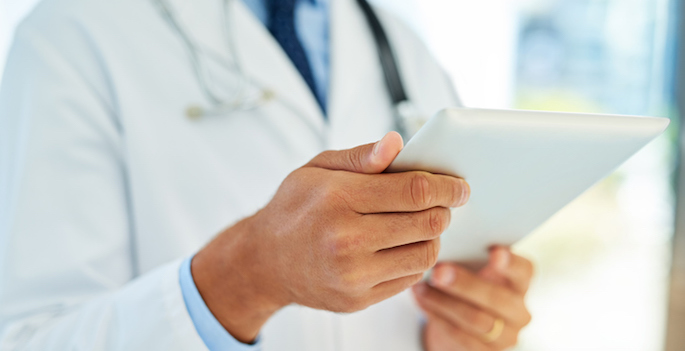 close up of male doctor looking at ipad