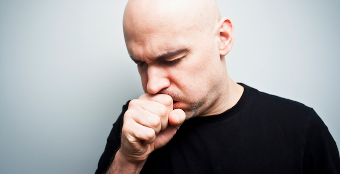 Man holds his hand over his mouth while coughing into it