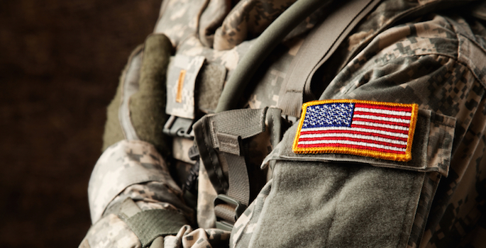 close-up of camouflauge uniform with american flag patch